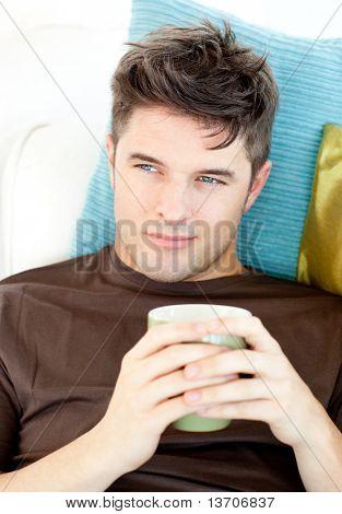 Charismatischen jungen Mann hält eine Tasse liegend auf dem Sofa im Wohnzimmer