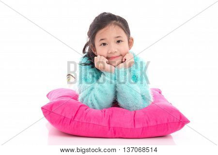 Beautiful asian girl lying on a big pink pillow white background isolated