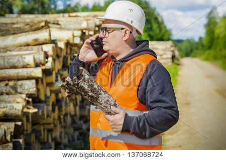 Lumberjack with tree bark and smart phone near log of pile