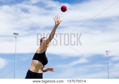 Confident female athlete throwing shot put ball in stadium