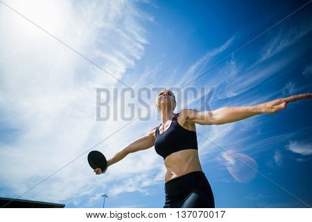 Female athlete about to throw a discus in stadium