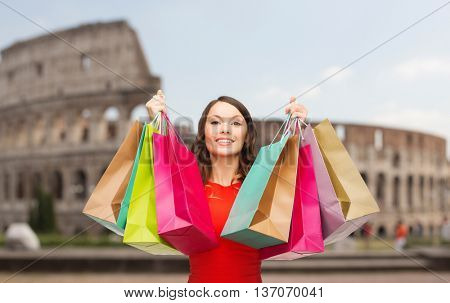people, holidays, tourism, travel and sale concept - young happy woman with shopping bags over coliseum background