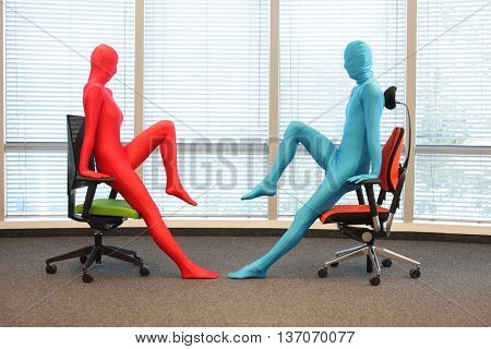 anonymous couple in full body lycre suits exercising with chairs in office