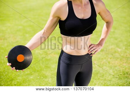 Mid section of female athlete about to throw a discus in stadium