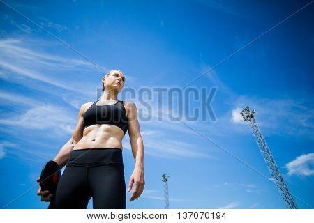 Female athlete holding a discus in stadium