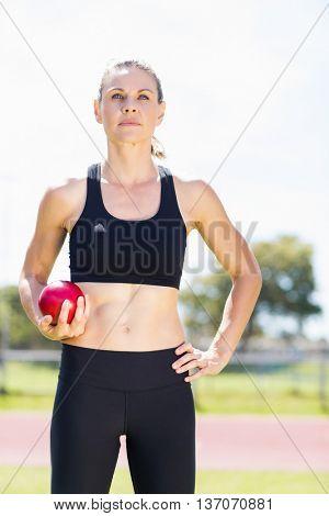 Confident female athlete holding a shot put ball in stadium