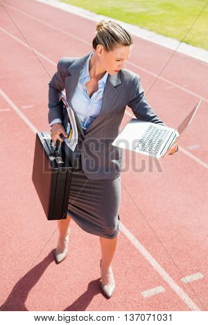 Businesswoman ready to run with a laptop and briefcase on running track
