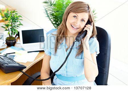 Lebhafte junge geschäftsfrau Gespräch am Telefon sitzen an ihrem Schreibtisch im Büro