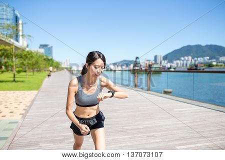 Woman using wearable watch when running outside