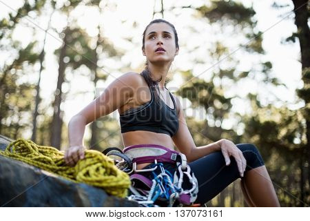 Woman sitting with climbing equipment on the wood