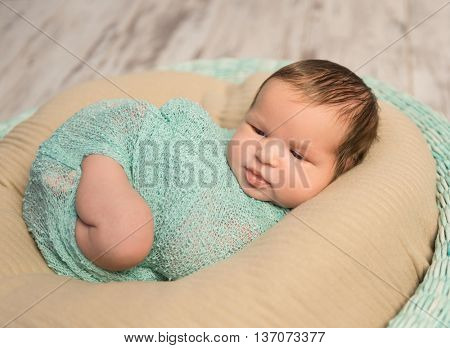 wrapped newborn baby with bare foot lying in round cot, top view