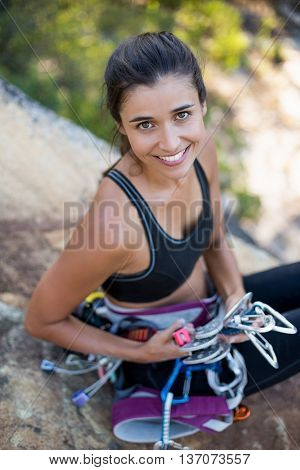 Woman smiling and sitting with climbing equipment on the wood