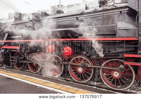 Retro steam locomotive stands by the platform.