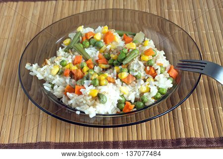 China white rise with vegetables in translucent plate on brown wicker straw mat and metal fork front view closeup