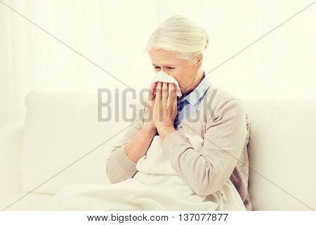 health care, flu, hygiene, age and people concept - sick senior woman blowing nose to paper napkin at home