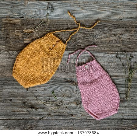 two colorful yellow and pik knitted overalls for newborn baby on wooden background, top view