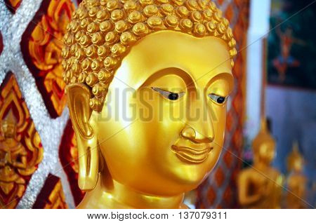 Close up Buddha face of a golden statue in the Wat Chalong temple, Phuket, Thailand.