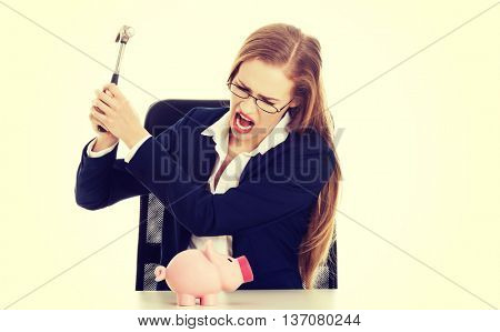 Business woman is trying to destroy piggy bank