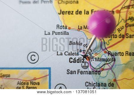 Pushpin marking on Cadiz Spain. Selective focus on city