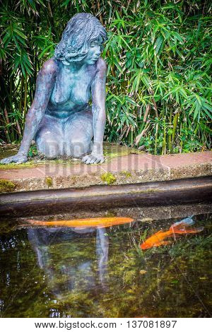 statue of a young girl looking over a pond in Queens Park Hamilton Bermuda.