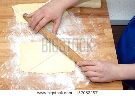 Female hands with rolling pin sheeting the dough preparing for baking on brown wooden cutting board on kitchen table. Closeup view