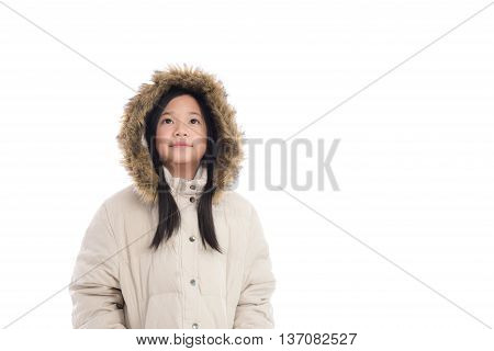 Beautiful asian girl in winter coat looking up on white background isolated