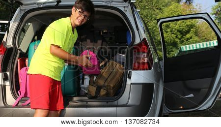 Young Boy With Glasses Loaded The Luggage In The Trunk