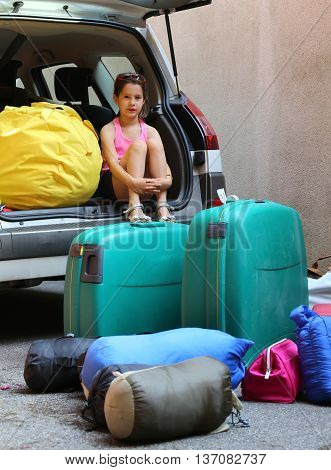 Little Girl Loads The Car During The Summer Holidays