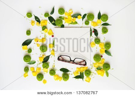 Glasses and paper with pattern from petals of roses and chrysanthemum flowers ficus leaves and ripe rowan on white background. Overhead view. Flat lay.