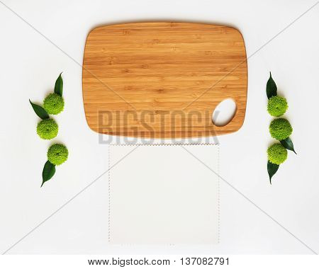 Wooden cutting board and paper with decoration of chrysanthemum flowers and ficus leaves on white background. Overhead view. Flat lay.