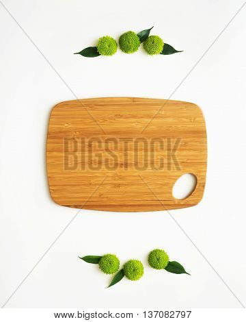 Wooden cutting board with decoration of chrysanthemum flowers and ficus leaves on white background. Overhead view. Flat lay.