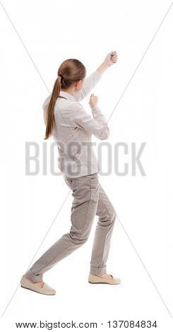 back view of standing girl pulling a rope from the top or cling to something. girl  watching. Rear view people collection.   Girl with long hair in a white jacket top left pulls on the rope.