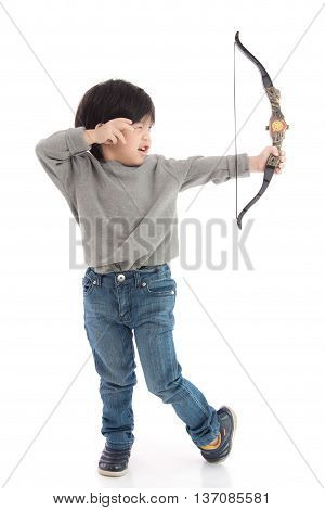 Cute asian boy playing toy bow on white background isolated