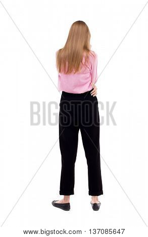 back view of standing young beautiful  woman.  girl  watching. Rear view people collection.  backside view of person.  The girl office worker in black trousers is hugging himself.