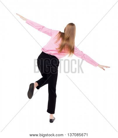 Balancing young business woman.  or dodge falling woman. Rear view people collection.  backside view of person.  The girl office worker in black pants standing on one leg, arms to the side.