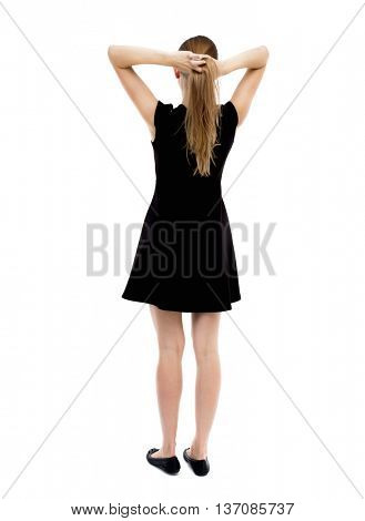 back view of standing young beautiful  woman.  girl  watching. Rear view people collection.  backside view of person.  The blonde in a black dress standing with his hands on his head.