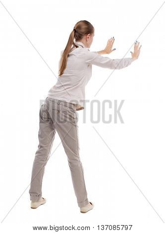 back view of woman pushes wall. Isolated over white background. Rear view people collection. backside view of person. Girl with long hair in a white jacket pushes away something left.