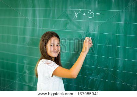 Happy schoolchild writing on blackboard. solve mathematical quests