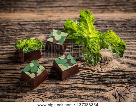 Chocolate pralines with mint on wooden background