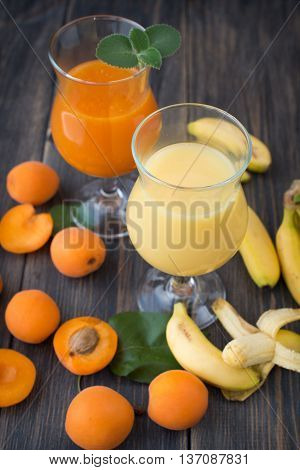 Fresh apricot and banana juice with mint Bananas and apricots on black background selective focus