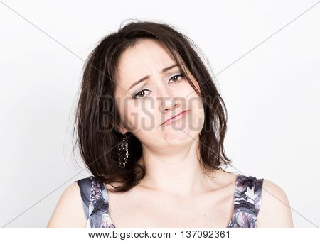 beautiful young brunette woman in a colorful dress posing and expresses different emotions. girl's hands shows various signs, close-up portret.