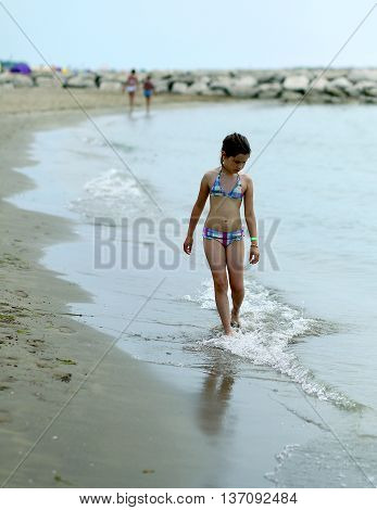thoughtful little girl in swimsuit on the shore of the sea in summer