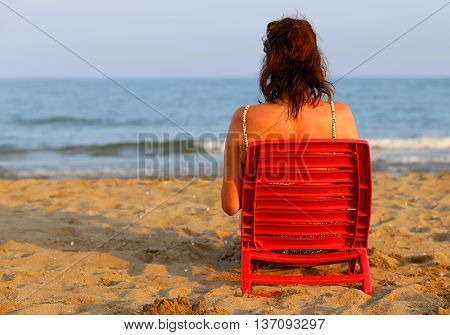 Woman Tanning On The Seashore At Sunset