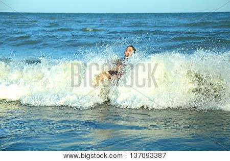 Happy Boy Plays By Jumping The Waves Of The Sea