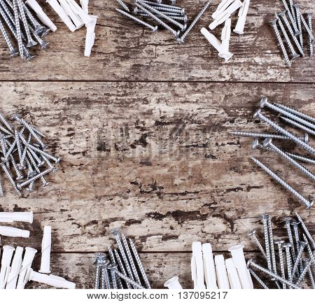 screws and dowels on a wooden background with copy space