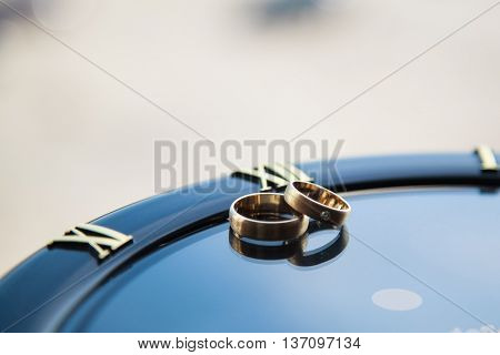 wedding rings on a dark background clock with Roman numerals