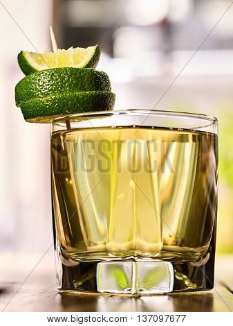 Healthy drink. On wooden boards is glass with green transparent drink. A drink number two cold green tea with lime. Country life. Light background.