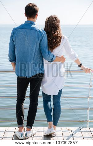 Full length of a young couple standing backwards hugging and looking ahead at the seaside