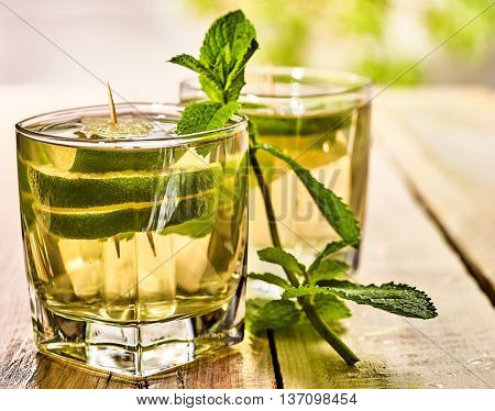 Alcohol drink. On wooden boards are two glasses with alcohol green transparent drink. A drink number seventeen mojito cocktail with lime and mint leaf . Country life. Light background.