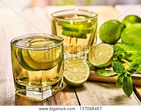 Country drink. On wooden boards are two glasses with green transparent drink and half lime glue bowl. A drink number twenty mojito with mint leaf on sunlight . Country life. Light background.